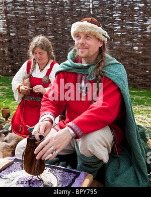 Man and woman dressed authentically as Vikings in the Viking Village at Largs Viking Festival, 2010, Man is casting - Stock Photo