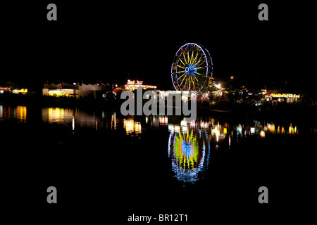 Nighttime Carnival Reflection. Fairgoers mill about a traveling carnival on Canada Day. A ferris wheel is reflected - Stock Photo