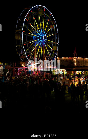 Evening at the Fair vertical. Fairgoers mill about a traveling carnival after dark on Canada Day. A ferris wheel - Stock Photo