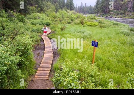 A woman runs along the Deschutes River Trail near downtown Bend, Oregon. - Stock Photo