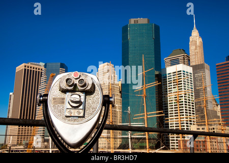 Pay Binoculars overlooking old sailing ships with the buildings of Lower Manhattan beyond, New York City, USA - Stock Photo