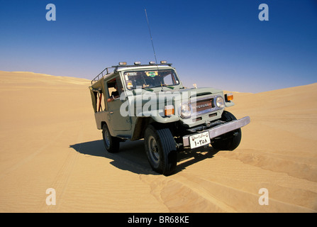 Land cruiser on dune near Siwa Oasis Egyptian Western Desert - Stock Photo