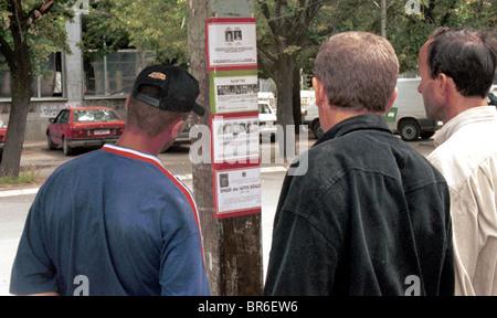 Albanian men read death notices in Pristina, Kosovo after the Kosovo war. - Stock Photo
