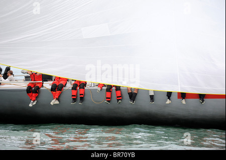 Legs of 'Luna Rossa' crew visible under sail, Cowes Week, August 2009. - Stock Photo