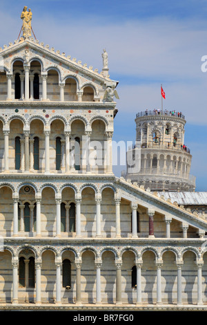 The Duomo with the iconic Leaning Tower behind it, in Pisa's Square of MIracles, Italy - Stock Photo