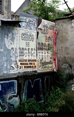 Circus posters on wall of abandoned derelict industrial looking building in Bergamo, northern Italy. - Stock Photo