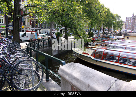 bikes lined up by canal Amsterdam, Holland, Netherlands - Stock Photo