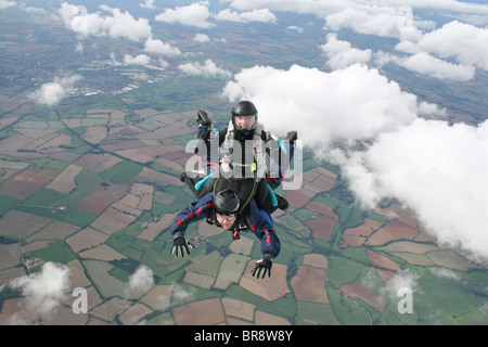 Two skydivers in freefall doing a rodeo - Stock Photo