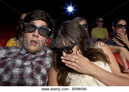 Shocked young couple in the movie theater - Stock Photo