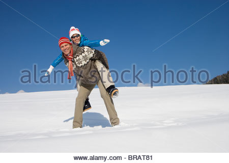 Man giving girlfriend piggyback ride while standing in snow - Stock Photo