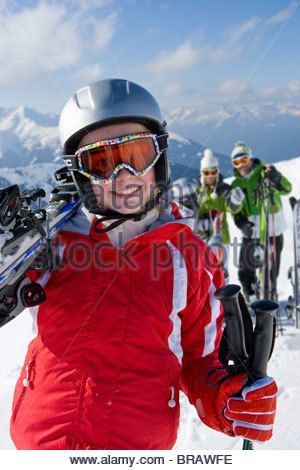 Family standing in snow on mountain top with skis - Stock Photo