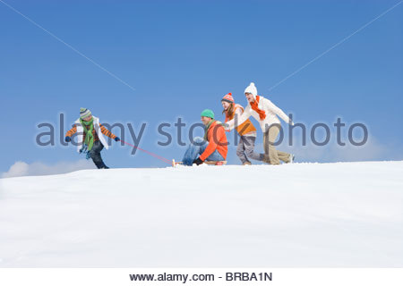Family playing with sled on ski slope - Stock Photo