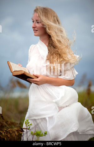 Girl in white dress holding a book - Stock Photo