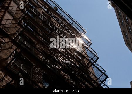 Iron Fire Escape glinting in the sun. A multistory steel fire escape zigzags down the side of an old Boston high - Stock Photo