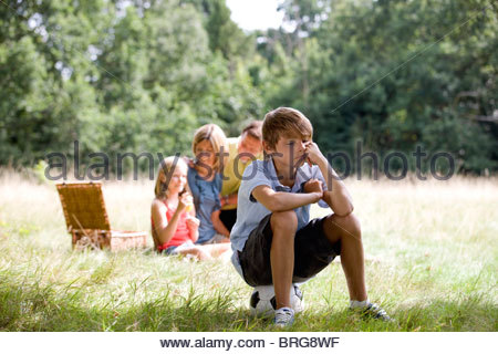 A family having a picnic, young boy sitting on a football looking bored - Stock Photo