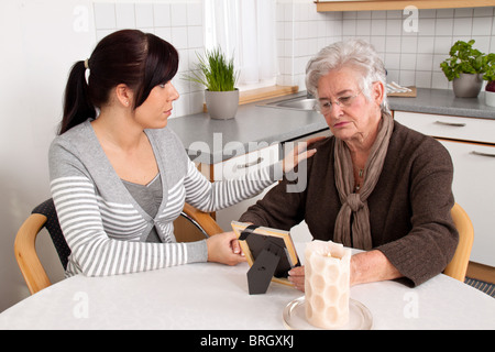 A young woman comforting a widow after event of death. Grief counseling. - Stock Photo