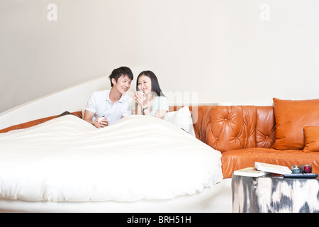 Young couple having coffee in bed - Stock Photo