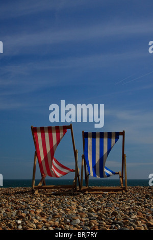 Two deckchairs on Brighton beach against a clear blue sky on a breezy day - Stock Photo