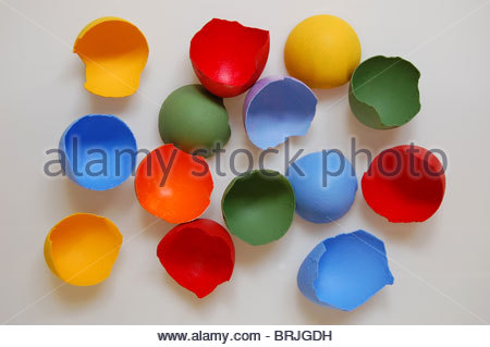 overhead studio shot assorted colored hand painted half egg shells on white background in red yellow blue green - Stock Photo