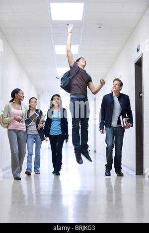 High school students in school corridor watching friend jumping - Stock Photo