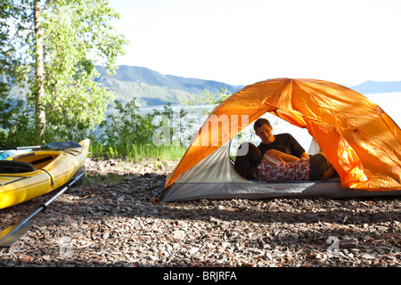 A young couple camping talk in their tent next to kayaks with lake in the background in Idaho. - Stock Photo