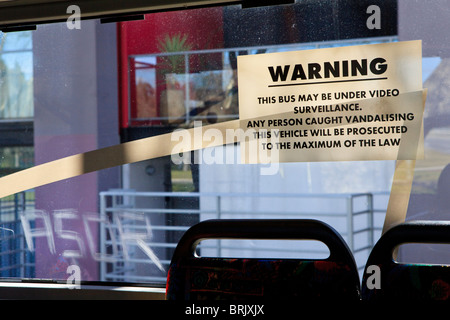 Video surveillance warning that all vandalism will be prosecuted next to graffiti scratched into the bus window - Stock Photo