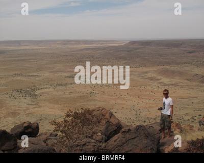 A Tourist standing at the edge of the Bandiagara escarpment - Stock Photo