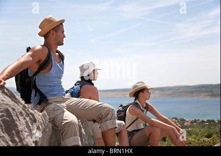 Hikers resting on coastal path - Stock Photo