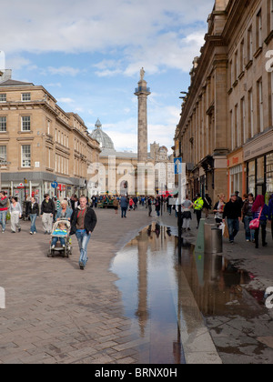 Grainger Street Newcastle upon Tyne with Lord Grey's Monument reflected in a puddle - Stock Photo
