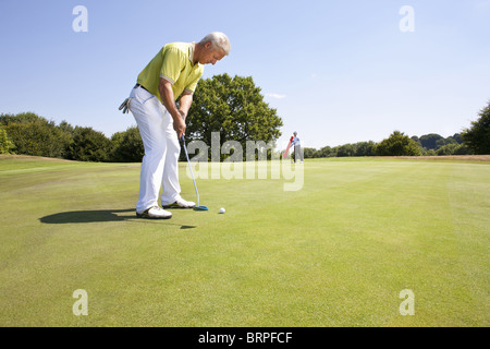 Caddy pointing at a hole on golf course - Stock Photo