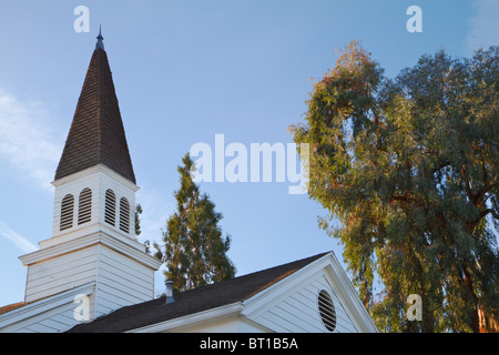 Old traditional community church steeple against blue sky and clouds and trees - Stock Photo