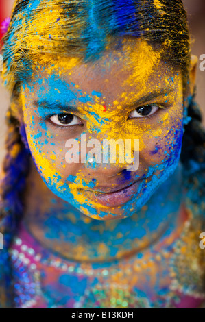 Young Indian girl covered in coloured powder pigment. India - Stock Photo
