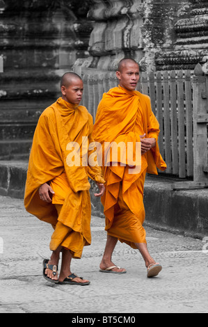 Two Young Buddhist Monks in Orange Robes in the Angkor Wat Temple Complex, Cambodia - Stock Photo