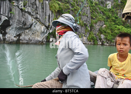 Mother and child using traditional methods to catch fish in Halong Bay, Vietnam - Stock Photo