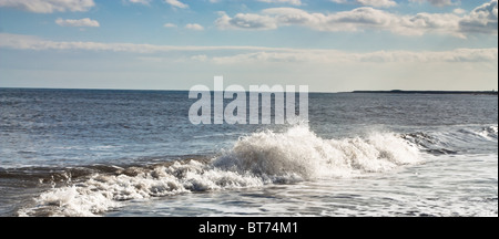 Surf and waves rolling onto sandy shore off Northumberland coast. - Stock Photo