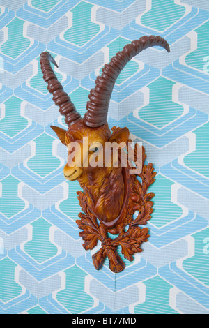Plastic head of an ibex mounted on kitschy wallpaper from the 1960s or 1970s - Stock Photo