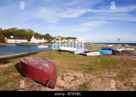 Upturned boats with view to The Ship Inn and village across small harbour in Red Wharf Bay, Isle of Anglesey, North - Stock Photo