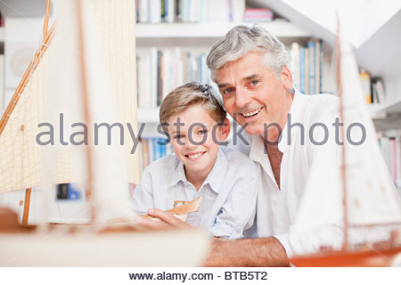 Smiling grandfather and grandson with model sailboats - Stock Photo