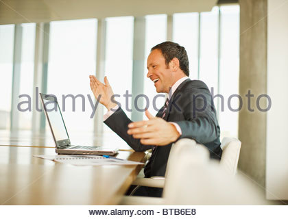 Happy businesswoman looking at laptop and gesturing - Stock Photo