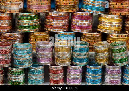 Coloured indian ladies bangles in rows on a market stall in India - Stock Photo