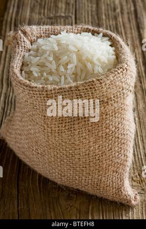 White long rice in burlap sack - Stock Photo