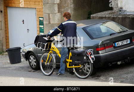 French postwoman riding her yellow painted bicycle in the rural town of Aizenay Vendee region of France - Stock Photo