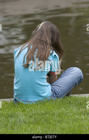 Back view depressed teenager: The anonymous teenage girl sitting sad at water side thinking, - Stock Photo