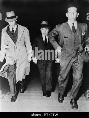 Lucky Luciano (1896-1962), being escorted into court by two detectives in 1936. Luciano was sentenced to 30-to-50 - Stock Photo