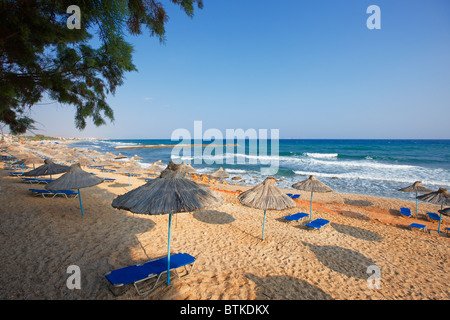 Thatched parasols and lounge chairs on a sandy beach near Hersonissos. Crete island, Greece. - Stock Photo
