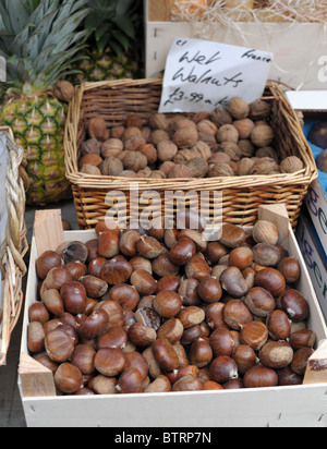 A box of chestnuts and basket of walnuts on a market stall in Clifton, Bristol. - Stock Photo