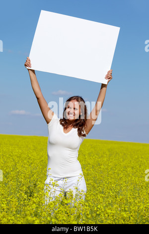 Portrait of charming girl with blank paper standing in the field - Stock Photo