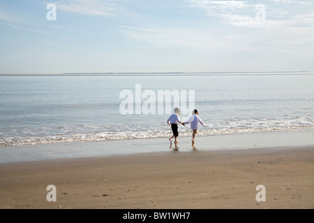 Two boys running on the beach - Stock Photo