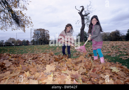 Two little girls in a park in Autumn raking leaves. - Stock Photo