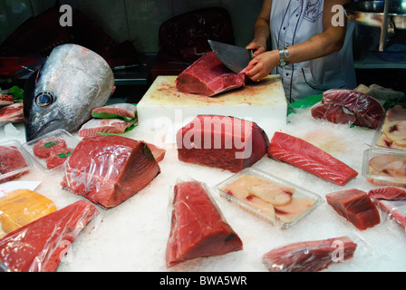 woman cuts a piece of fresh tuna fish with large knife at stall in La Boqueria market hall in Barcelona, Spain - Stock Photo